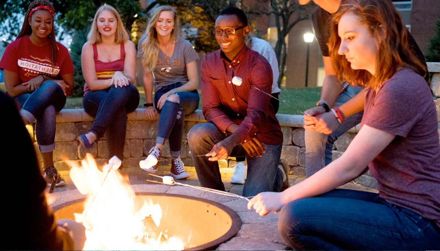 Students gathered around the fire pit roasting marshmallows