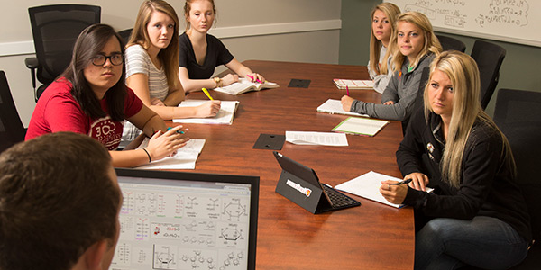 Students listening to a presentation in a conference room
